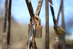 Old rusty padlock closed on the grate royalty free stock images