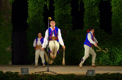 Polish dancers jump with crooks. Folkloric male dancers jumping with crooks on the stage of the Summer Theatre, Varna during the 24th edition of the royalty free stock image