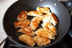 Polish dish pirogi in frying pan. Preparing traditional polish meal pirogi. Food preparing conceptual images. royalty free stock image