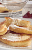Polish doughnuts with icing sugar. The close-up view of Polish doughnuts (racuchy) poured with icing sugar. Tight frame with background out of focus royalty free stock photography