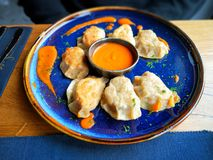 Polish dumplings - pierogi, on blue plate. Polish dumplings - pierogi, on blue ceramic plate in restaurant stock image