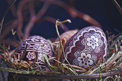 Easter eggs in a metal basket on a wooden table Royalty Free Stock Image