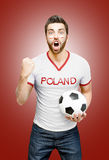 Polish fan holding a soccer ball celebrates on red background Stock Image