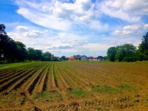 Polish Farm Field. A view of ploughed fields against a blue cloudy summer sky and farmhouse in rural Poland stock photography