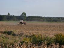 Polish farmer in a tractor working in the field. stock image