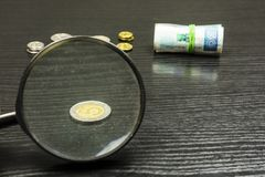 Polish five zloty through a magnifying glass. Polish five zloty, through a magnifying glass in the background, other coins and rolls of banknotes Stock Image