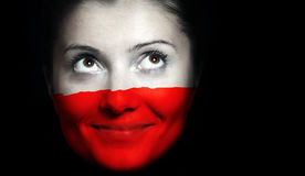 Polish flag. A close up of a Polish flag on a femal face over black background royalty free stock photography