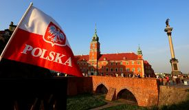 Polish flag with the coat of arms. Against the background of the old city of the fortress and the bridge stock photo