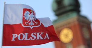 Polish flag with the coat of arms. Polish flag against the bell tower royalty free stock photos
