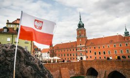 Polish flag in front of The Royal castle. Old town in Warsaw. Royalty Free Stock Image