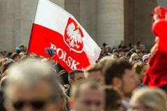 A Polish Flag. Vatican City, Vatican - February 22, 2015: A crowd gathers in St. Peter`s Square while someone waves a Polish flag in the sun royalty free stock image