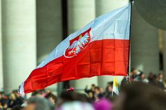 A Polish Flag. Vatican City, Vatican - February 22, 2015: A crowd gathers in St. Peter`s Square while someone waves a Polish flag in the sun stock photo