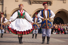 Polish folk collective on Main square during annual Polish national and public holiday the Constitution Day. KRAKOW, POLAND - MAY 3, 2015: Polish folk collective stock photo
