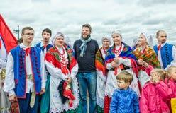 Polish folk dance ensemble GAIK shooting with an occasional tourist at the Dvortsovaya embankment. Stock Photo