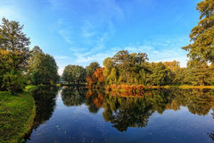 Polish golden autumn. Pond in the autumn park with small island in background Stock Images