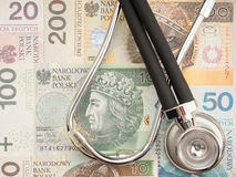 Polish healthcare costs. Stethoscope draped on zloty banknotes, for your healthcare costs copy - focus is on the money Royalty Free Stock Image