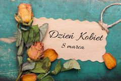 Polish International Women`s Day card,. With word: Women;s day. Dried orange roses and paper card on wooden background Royalty Free Stock Images