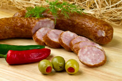 Polish kielbasa. With olives and chilli peppers Royalty Free Stock Photography