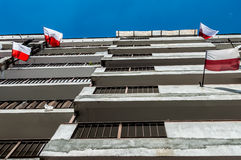 Polish national flags at block of flats during Independence Day and blue sky Stock Photos