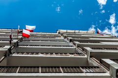 Polish national flags at block of flats during Independence Day and blue sky Royalty Free Stock Image