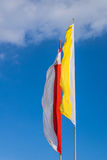 Polish and Papal flags. Waving in the wind at the blue sky stock photo