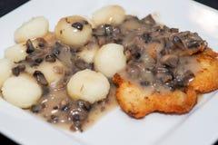 Polish Potato Drop Dumplings and Breaded Chicken Breast in Mushroom Sauce on plate. Polish Potato Drop Dumplings and Breaded Chicken Breast in Mushroom Sauce on stock photography