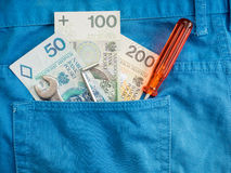 Polish repair costs. Zloty banknotes and tools sticking out of a workers jeans back pocket - for concepts involving construction, renovation and repair costs royalty free stock image