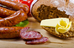 Polish sausage. Tasty Polish sausage with bread, butter and vegetables Royalty Free Stock Images