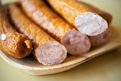 Polish Sausage. On the Wood Plate.  Pieces ( Kielbasa ) on Wood Table Stock Photo