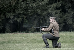 Polish soldier firing burst from Thompson machine gun during historical reenactment of WWII Royalty Free Stock Photos