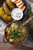 Polish soup with sour cucumbers on the table. vertical top view Royalty Free Stock Images