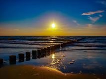 Sunset Baltic Sea. Wooden piles lead to horizon Royalty Free Stock Photos