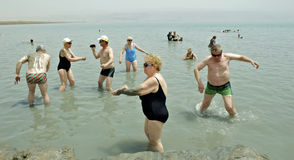 A Polish Tourist Group enjoy the mud of the Dead Sea. Stock Photo