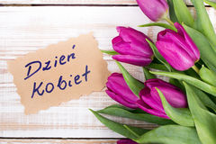 Polish Women`s Day card and a bouquet of beautiful tulips on wooden background Royalty Free Stock Photo