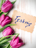 Polish words I MISS YOU and bouquet of tulips. On wooden background Stock Photography
