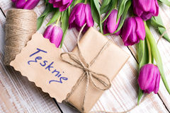 Polish words I MISS YOU and bouquet of tulips on wooden background Royalty Free Stock Photography
