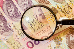 Polish zloty banknotes currency and magnifying glass Stock Photography