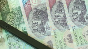 Polish zloty banknotes with magnifying glas. Full HD with motorized slider 1080p stock video footage