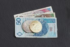 Polish zloty and bitcoin on the black slate stone background. Top view Stock Photos