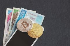 Polish zloty and bitcoin on the black slate stone background. Top view Royalty Free Stock Photography