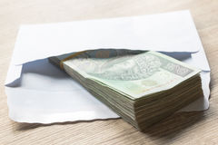 Polish zloty currency hundred notes in white envelop on table. C Royalty Free Stock Photography