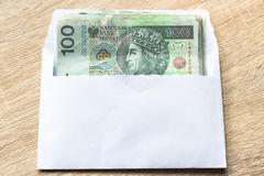 Polish zloty currency hundred notes in white envelop on table. C Stock Image
