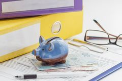 Polish zloty, folders, piggy bank and glasses Stock Photos