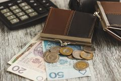 Polish zloty with little wallets and calculator on the wooden background Royalty Free Stock Photography