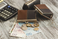 Polish zloty with little wallets and calculator on the wooden background Royalty Free Stock Images