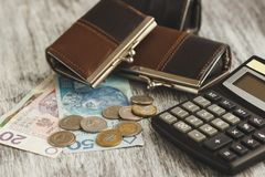 Polish zloty with little wallets and calculator on the wooden background Royalty Free Stock Photo