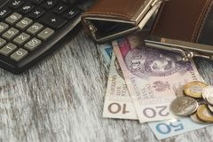 Polish zloty with little wallets and calculator on the wooden background stock image