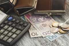 Polish zloty with little wallets and calculator on the wooden background Stock Photos