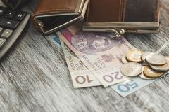 Polish zloty with little wallets and calculator on the wooden background Royalty Free Stock Image