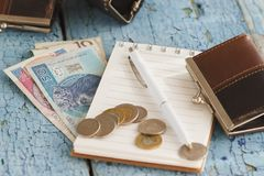 Polish zloty with little wallets and notebook on the wooden background Royalty Free Stock Photo